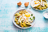 Mexican fried corn chips with tomatillo sauce, sour cream, cheese, and onions, topped with fried eggs