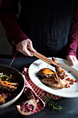 Arranging pomegranate, walnut, and guinea fowl on a plate with rosemary