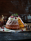 Christmas spongecake with frosting, rosemary icing sugar, saffron and cranberries