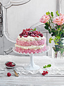 Spongecake with coconut flakes, raspberries, red currants and frosting