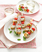 Pancake rolls on skewers with tomato and basil