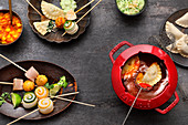 Fondue with a spicy broth: fish and vegetable rolls, chicken and pastry parcels