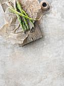 Grüner Spargel auf Papier mit Küchengarn