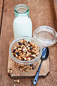 Granola with dried cranberries in a glass jar in front of a milk bottle