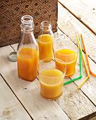 Gelber Fruchtsaft in der Flasche und im Glas