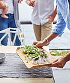 Frau serviert Austern mit Gurken-Schalotten-Salat auf Holzbrett