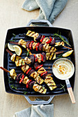 Chicken skewers with peppers and red onions in a grill pan