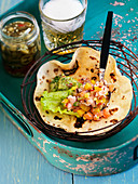 Texmex tortilla with salmon ceviche, guacamole, beer and jalapenos