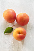 Three apricots with a leaf