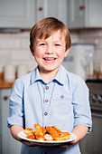 Boy holding plate with chicken schnitzel strips