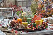 Tischdekoration mit Kerzen, Kürbis, Hagebutten, Maronen und Herbstlaub auf großem Untersetzer