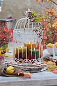 Kerzen im Dekokäfig auf Holzscheibe als Tischdekoration