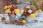 Kleine Rosensträuße in Tassen: Rosenblüten, Hagebutten, Zierquitten und Ranke vom wilden Wein