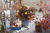 Herbststrauß aus Hagebutten und Rosen in Korbvase