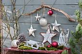 Weihnachtsdekoration mit Sternen, Kugeln, Zweigen, Zapfen, Moos und Schlitten