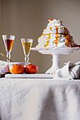 Pavlova cake with cardamom and sharon fruit puree on a cake stand