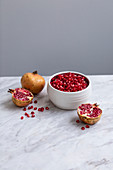 Pomegranate seeds in a ceramic bowl, with whole and halved pomegranates