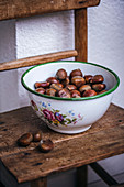 Fresh chestnuts in a vintage bowl on a wooden chair