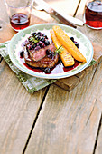 Beef steak with a red wine and blueberry sauce and grilled polenta