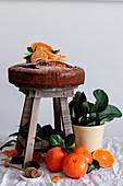 Mandarinenkuchen auf Holzhocker, umgeben von frischen Mandarinen