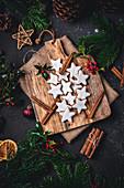 Cinnamon stars with cinnamon sticks on a wooden board