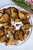 Roasted oyster mushrooms with rosemary served on a white plate