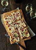 Flammkuchen mit Speck und Zwiebeln auf Holzbrett und drei Weissweingläser