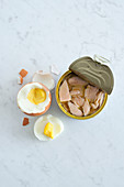 An arrangement with an open tin of tuna and a hard-boiled egg