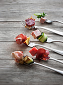 Savoury fork canapés with salami, ham, sausage, fruit and vegetables