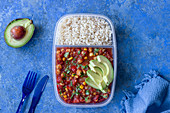 Lunchbox with easy chickpea and corn chilli, parsley, avocado, brown rice