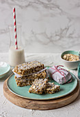 Homemade muesli bars from nuts and dried fruits with oats, milk in a glass