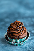 A vegan chocolate cupcake with frosting and chocolate sauce