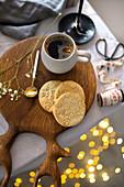 Eine Tasse Kaffee auf Holzbrett mit Keksen (weihnachtlich)