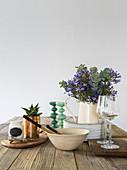 Schlichte Küchenutensilien und Blumenstrauß auf dem Holztisch