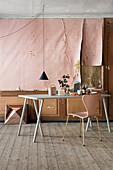 Tisch und Stuhl im Altbau mit abgelöster rosa Tapete