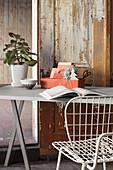 Buch, Utensilo und Pflanze auf dem Schreibtisch vor abgenutzter Tür