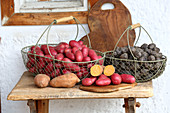 Colourful potatoes in wire baskets on rustic wooden bench