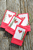 Hearts printed on paper with pinked edges tucked into linen napkins
