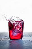 Roter Drink mit Splash vor weißem Hintergrund