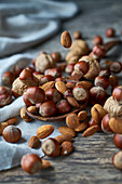 Hazelnuts, almonds and walnuts on a wooden spoon and a table