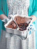 Frau serviert Self Saucing Schokoladenpudding