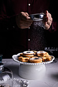 Dusting Linzer cookies with powder sugar