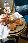 A copper pot, tea glasses and cake on a stylish side table