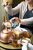 A stylish teatime with a copper pot, tea glasses and cake