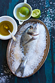 Sea bream in salt with olive oil and limes