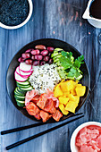 Hawaiian poke bowl with basmati rice, mango, raw salmon, avocado, radishes, cucumber and kalamata olives