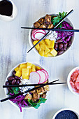 Vegan poke bowl with basmati rice, mango, fried tofu, purple cabbage, radishes, olives, pickled ginger and black sesame