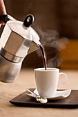 Hot coffee being poured from a mocha jug