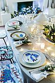 Weihnachtlich gedeckter Tisch mit Gesteck, Lichterkette und individuellen Platztellern