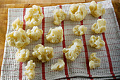 Blanched cauliflower florets on a tea towel
